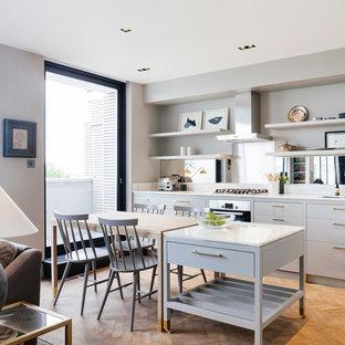 Diseño de cocina comedor lineal, actual, pequeña, con puertas de armario grises, encimera de mármol, salpicadero metalizado, salpicadero con efecto espejo, electrodomésticos con paneles, suelo de madera en tonos medios y una isla