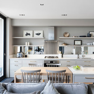 This is an example of a contemporary single-wall open plan kitchen in London with a double-bowl sink, flat-panel cabinets, grey cabinets, metallic splashback, mirror splashback, stainless steel appliances, medium hardwood flooring and an island.