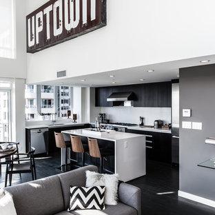 バンクーバーの中サイズのエクレクティックスタイルのおしゃれなキッチン (フラットパネル扉のキャビネット、黒いキャビネット、人工大理石カウンター、シルバーの調理設備、濃色無垢フローリング、黒い床、グレーのキッチンパネル) の写真