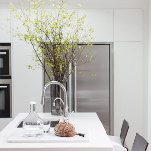 Mid-sized contemporary open plan kitchen in London with a drop-in sink, flat-panel cabinets, white cabinets, stainless steel appliances, terra-cotta floors and a peninsula.