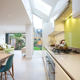 ロンドンの大きいコンテンポラリースタイルのおしゃれなダイニングキッチン (ガラスタイルのキッチンパネル、磁器タイルの床、アイランドなし、アンダーカウンターシンク、フラットパネル扉のキャビネット、白いキャビネット、クオーツストーンカウンター、黄色いキッチンパネル、シルバーの調理設備の、ベージュの床) の写真