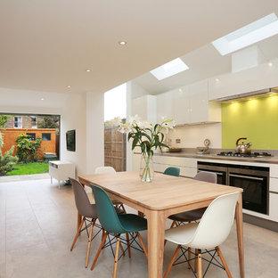 ロンドンの広いコンテンポラリースタイルのおしゃれなダイニングキッチン (白いキャビネット、セラミックタイルの床、ドロップインシンク、フラットパネル扉のキャビネット、クオーツストーンカウンター、黄色いキッチンパネル、ガラス板のキッチンパネル、シルバーの調理設備、アイランドなし、ベージュの床) の写真