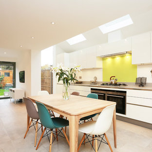 Inspiration for a large contemporary single-wall eat-in kitchen in London with yellow splashback, white cabinets, quartz benchtops, glass sheet splashback, stainless steel appliances, no island and beige floor.