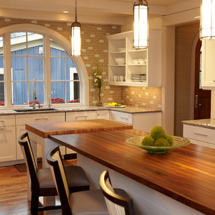 Example of a coastal kitchen design in Grand Rapids with wood countertops