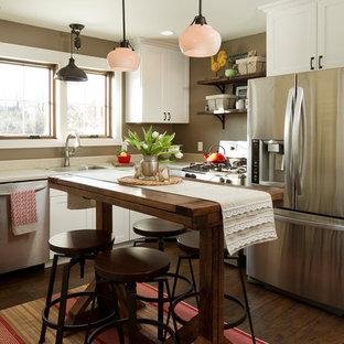 ミネアポリスのカントリー風おしゃれなL型キッチン (シングルシンク、シェーカースタイル扉のキャビネット、白いキャビネット、シルバーの調理設備の、濃色無垢フローリング、白いキッチンカウンター) の写真