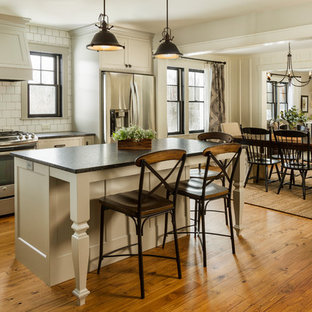 Photo of a country open plan kitchen in Minneapolis with shaker cabinets, grey cabinets, white splashback, stainless steel appliances, medium hardwood flooring, an island and black worktops.