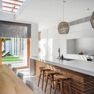 Inspiration for a beach style galley kitchen in Sunshine Coast with an undermount sink, flat-panel cabinets, white cabinets, white splashback, panelled appliances, with island, grey floor and white benchtop.