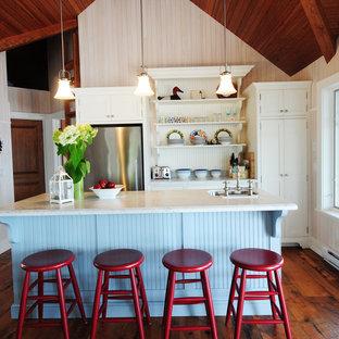 Exemple d'une petite cuisine ouverte parallèle bord de mer avec un évier encastré, un placard à porte shaker, des portes de placard blanches, un électroménager en acier inoxydable, un sol en bois foncé, un îlot central, un plan de travail en quartz modifié et un sol marron.