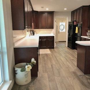 他の地域の中サイズのカントリー風おしゃれなキッチン (アンダーカウンターシンク、レイズドパネル扉のキャビネット、濃色木目調キャビネット、クオーツストーンカウンター、白いキッチンパネル、セラミックタイルのキッチンパネル、黒い調理設備、無垢フローリング、茶色い床、白いキッチンカウンター) の写真