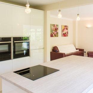 Esempio di una cucina moderna di medie dimensioni con lavello da incasso, ante beige, top in laminato, paraspruzzi beige, elettrodomestici neri, pavimento in compensato, isola, pavimento beige e top beige