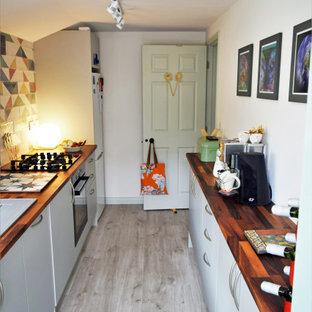 ドーセットの小さいトラディショナルスタイルのおしゃれなキッチン (ダブルシンク、フラットパネル扉のキャビネット、青いキャビネット、木材カウンター、マルチカラーのキッチンパネル、モザイクタイルのキッチンパネル、パネルと同色の調理設備、クッションフロア、アイランドなし、グレーの床、マルチカラーのキッチンカウンター) の写真