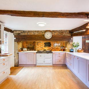 Exemple d'une cuisine nature en L avec un placard à porte shaker, des portes de placard violettes, un plan de travail en quartz, un plan de travail blanc, une crédence en brique, un électroménager noir, un sol en bois brun et aucun îlot.