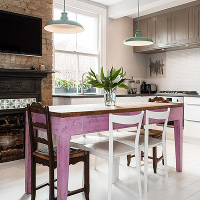 Inspiration for a mid-sized country l-shaped painted wood floor enclosed kitchen remodel in London with an undermount sink, shaker cabinets, granite countertops, white backsplash, mosaic tile backsplash and stainless steel appliances