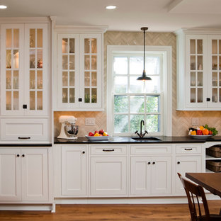 Inredning av ett klassiskt kök, med luckor med profilerade fronter, vita skåp, bänkskiva i kalksten, beige stänkskydd och stänkskydd i kalk