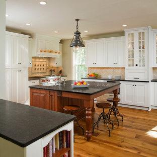 Inspiration för klassiska kök, med luckor med profilerade fronter, vita skåp, bänkskiva i kalksten, beige stänkskydd och rostfria vitvaror