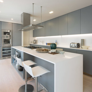 Contemporary kitchen in London with flat-panel cabinets, grey cabinets, white splashback, stainless steel appliances, light hardwood flooring, an island, beige floors and white worktops.