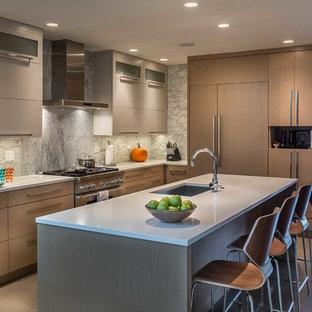 Modelo de cocina en L, actual, de tamaño medio, abierta, con fregadero bajoencimera, armarios con paneles lisos, puertas de armario marrones, encimera de vidrio reciclado, salpicadero verde, salpicadero de losas de piedra, electrodomésticos con paneles, suelo de cemento y una isla