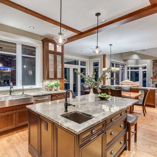 Inspiration for a large traditional u-shaped eat-in kitchen in Vancouver with a farmhouse sink, beaded inset cabinets, dark wood cabinets, limestone benchtops, multi-coloured splashback, matchstick tile splashback, stainless steel appliances, medium hardwood floors, with island, brown floor and multi-coloured benchtop.