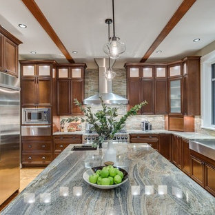 Large traditional u-shaped eat-in kitchen in Vancouver with a farmhouse sink, beaded inset cabinets, dark wood cabinets, limestone benchtops, multi-coloured splashback, matchstick tile splashback, stainless steel appliances, medium hardwood floors, with island, brown floor and multi-coloured benchtop.