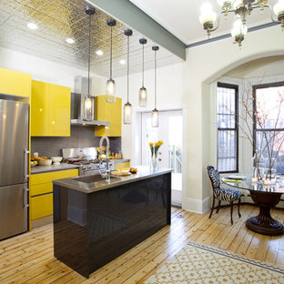 Contemporary galley eat-in kitchen in New York with an integrated sink, flat-panel cabinets, yellow cabinets, stainless steel benchtops, grey splashback and stainless steel appliances.