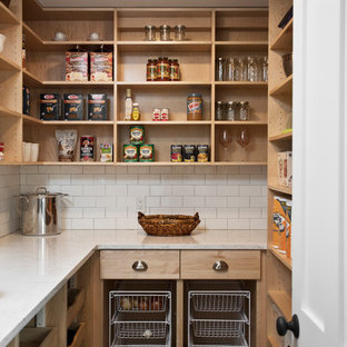 Mid-sized farmhouse kitchen pantry pictures - Example of a mid-sized cottage u-shaped dark wood floor and brown floor kitchen pantry design in New York with flat-panel cabinets, medium tone wood cabinets, white backsplash, subway tile backsplash, no island and white countertops