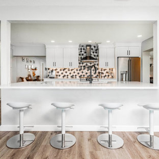 Large transitional kitchen pantry ideas - Example of a large transitional vinyl floor and brown floor kitchen pantry design in Orlando with an undermount sink, shaker cabinets, white cabinets, quartzite countertops, multicolored backsplash, porcelain backsplash, stainless steel appliances, an island and white countertops