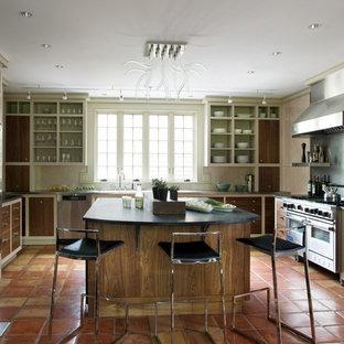 Foto di una cucina ad U stile rurale chiusa con elettrodomestici in acciaio inossidabile, nessun'anta, ante in legno bruno, top in saponaria e pavimento in terracotta