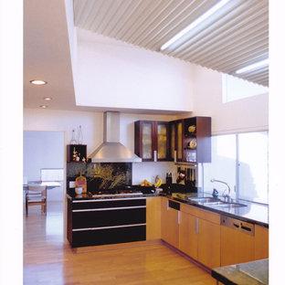 Exemple d'une grande cuisine tendance en U avec un évier 3 bacs, un placard à porte plane, des portes de placard en bois clair, un plan de travail en quartz, une crédence en fenêtre, un électroménager en acier inoxydable, un sol en bois clair, une péninsule et un sol beige.