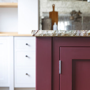 Photo of a mid-sized traditional open plan kitchen in Other with a double-bowl sink, shaker cabinets, purple cabinets, granite benchtops, metallic splashback, glass tile splashback, stainless steel appliances, light hardwood floors, with island, grey floor and green benchtop.