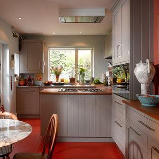 ロンドンの小さいコンテンポラリースタイルのおしゃれなダイニングキッチン (落し込みパネル扉のキャビネット、グレーのキャビネット、ステンレスカウンター、ガラス板のキッチンパネル、アイランドなし、赤い床) の写真
