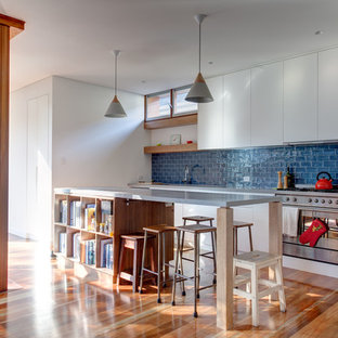 Contemporary galley open plan kitchen in Sydney with flat-panel cabinets, white cabinets, blue splashback, stainless steel appliances, medium hardwood floors, with island, brown floor and grey benchtop.