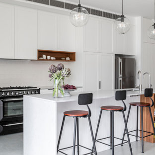 Inspiration for a mid-sized transitional single-wall open plan kitchen in Sydney with an undermount sink, shaker cabinets, white cabinets, quartz benchtops, white splashback, ceramic splashback, black appliances, concrete floors, with island, grey floor and grey benchtop.