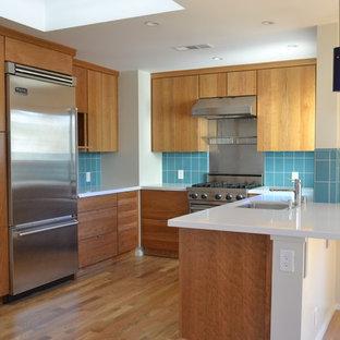 サンフランシスコの小さいエクレクティックスタイルのおしゃれなキッチン (アンダーカウンターシンク、フラットパネル扉のキャビネット、中間色木目調キャビネット、クオーツストーンカウンター、青いキッチンパネル、セラミックタイルのキッチンパネル、シルバーの調理設備、塗装フローリング、茶色い床、白いキッチンカウンター) の写真