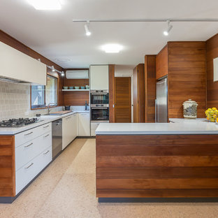 Inspiration for a mid-sized contemporary u-shaped kitchen in Melbourne with quartz benchtops, beige splashback, ceramic splashback, stainless steel appliances, cork floors, beige floor, white benchtop, flat-panel cabinets, white cabinets and a peninsula.