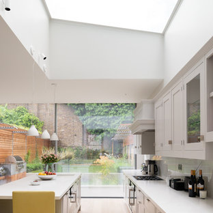 Classic galley kitchen in London with a submerged sink, shaker cabinets, white cabinets, light hardwood flooring, an island, beige floors and white worktops.