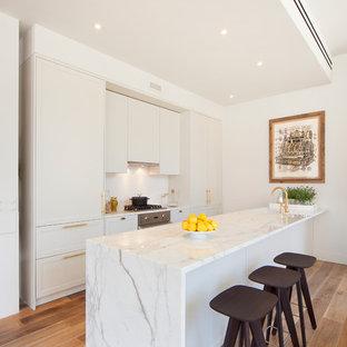 Idées déco pour une cuisine ouverte parallèle moderne de taille moyenne avec un évier 1 bac, un placard à porte shaker, des portes de placard blanches, un plan de travail en marbre, une crédence blanche, un électroménager en acier inoxydable, un sol en bois brun et une péninsule.