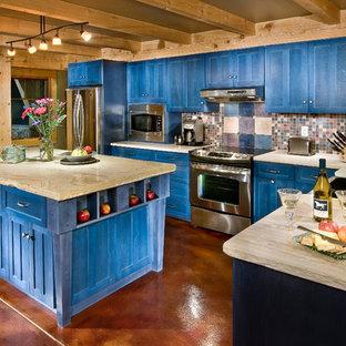 デンバーの中くらいのエクレクティックスタイルのおしゃれなキッチン (エプロンフロントシンク、シェーカースタイル扉のキャビネット、青いキャビネット、珪岩カウンター、マルチカラーのキッチンパネル、モザイクタイルのキッチンパネル、シルバーの調理設備、コンクリートの床、赤い床) の写真