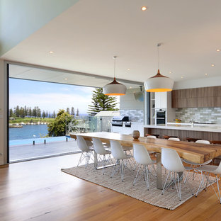 Medium sized contemporary galley kitchen/diner in Wollongong with a double-bowl sink, flat-panel cabinets, medium wood cabinets, engineered stone countertops, grey splashback, terracotta splashback, stainless steel appliances, medium hardwood flooring and an island.