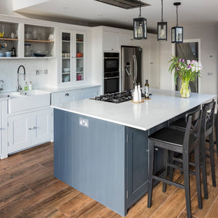 Design ideas for a medium sized traditional l-shaped kitchen/diner in London with a double-bowl sink, shaker cabinets, white cabinets, marble worktops, stainless steel appliances, medium hardwood flooring, an island and brown floors.