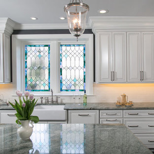 Inspiration for a mid-sized traditional u-shaped separate kitchen in Philadelphia with a farmhouse sink, raised-panel cabinets, white cabinets, granite benchtops, white splashback, porcelain splashback, stainless steel appliances, travertine floors and with island.