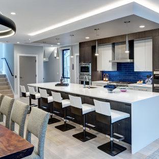 Пример оригинального дизайна: большая параллельная кухня в современном стиле с плоскими фасадами, фасадами цвета дерева среднего тона, синим фартуком, островом, белой столешницей, врезной раковиной, техникой из нержавеющей стали и зеленым полом