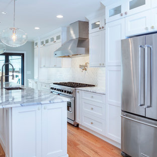 Mittelgroße, Offene, Zweizeilige Klassische Küche mit Unterbauwaschbecken, Schrankfronten mit vertiefter Füllung, weißen Schränken, Marmor-Arbeitsplatte, Küchenrückwand in Weiß, Rückwand aus Marmor, Küchengeräten aus Edelstahl, Kücheninsel, braunem Boden, weißer Arbeitsplatte und braunem Holzboden in Philadelphia