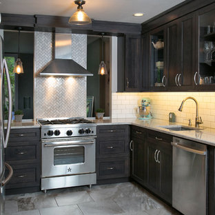 This is an example of a small transitional u-shaped eat-in kitchen in Philadelphia with an undermount sink, shaker cabinets, dark wood cabinets, marble benchtops, white splashback, porcelain splashback, stainless steel appliances and marble floors.
