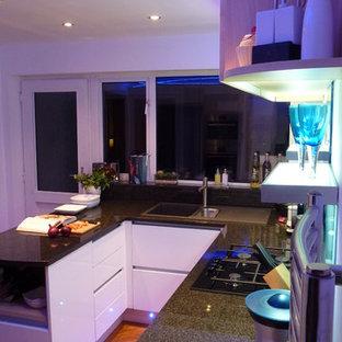 ウエストミッドランズの中くらいのコンテンポラリースタイルのおしゃれなキッチン (一体型シンク、フラットパネル扉のキャビネット、淡色木目調キャビネット、木材カウンター、青いキッチンパネル、ガラス板のキッチンパネル、シルバーの調理設備、クッションフロア、茶色い床、グレーのキッチンカウンター) の写真