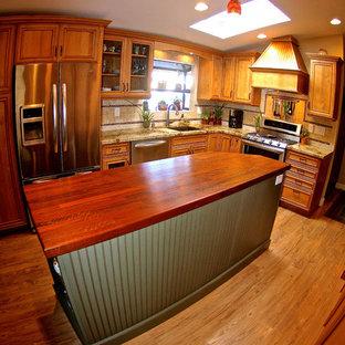 Diseño de cocina en L, rústica, de tamaño medio, abierta, con fregadero integrado, armarios con paneles lisos, puertas de armario de madera oscura, encimera de granito, salpicadero beige, salpicadero de azulejos de cerámica, electrodomésticos de acero inoxidable, suelo de madera clara y una isla