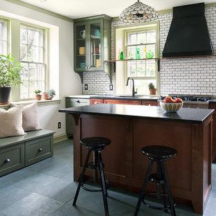 フィラデルフィアの中くらいのヴィクトリアン調のおしゃれなキッチン (アンダーカウンターシンク、落し込みパネル扉のキャビネット、中間色木目調キャビネット、白いキッチンパネル、シルバーの調理設備、サブウェイタイルのキッチンパネル、セラミックタイルの床、グレーの床、人工大理石カウンター) の写真