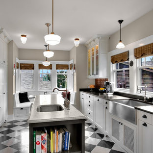 Photo of an arts and crafts separate kitchen in Seattle with glass-front cabinets, stainless steel appliances, a farmhouse sink, soapstone benchtops and multi-coloured floor.