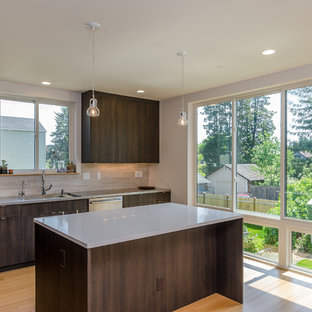 Mid-sized modern l-shaped open plan kitchen in Seattle with an integrated sink, flat-panel cabinets, dark wood cabinets, quartz benchtops, beige splashback, porcelain splashback, stainless steel appliances, bamboo floors and with island.