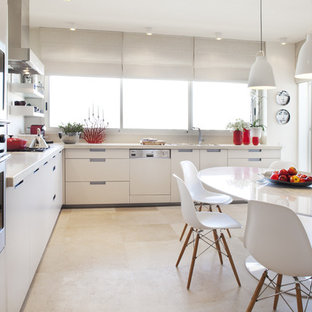 Modern eat-in kitchen in Tel Aviv with panelled appliances, flat-panel cabinets and white cabinets.