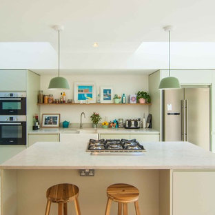 Design ideas for a medium sized modern single-wall kitchen in London with a double-bowl sink, flat-panel cabinets, green cabinets, granite worktops, stainless steel appliances, painted wood flooring, an island and white floors.